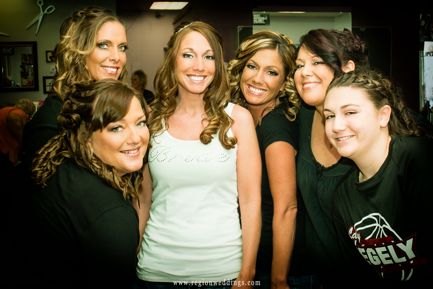 Bridesmaids gather around the bride for a group hug on her big day.