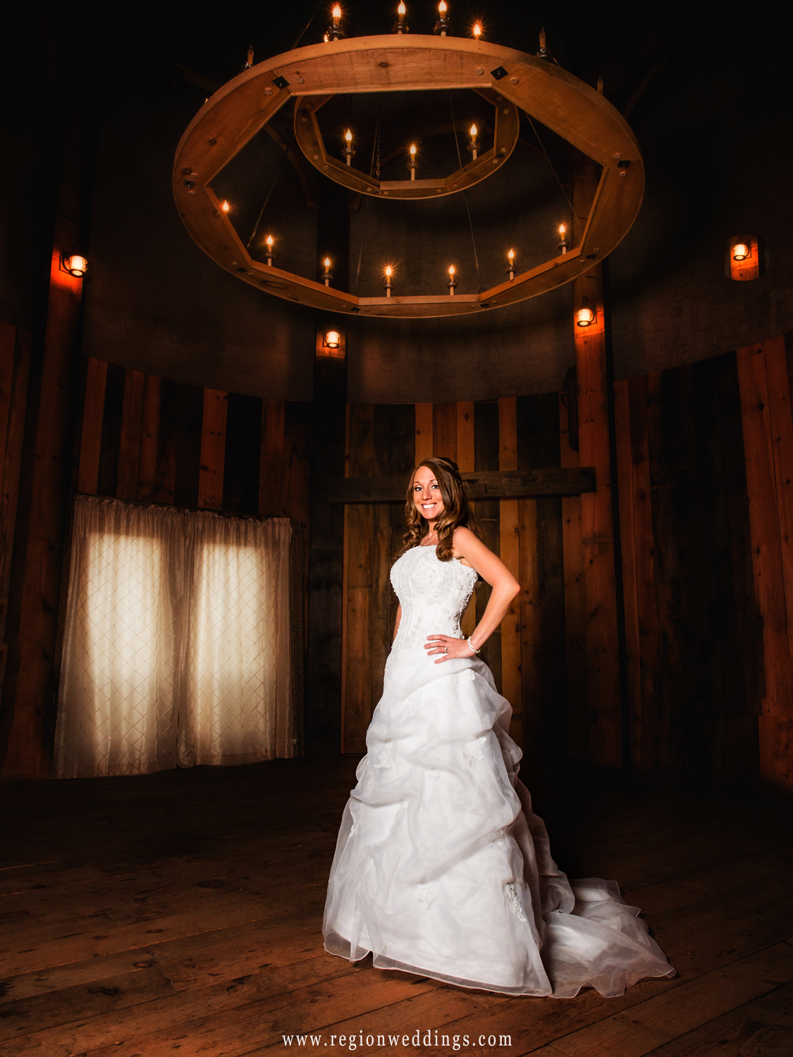 The bride stands beneath a lighted chandelier inside the bridal suite at County Line Orchard in Hobart, Indiana.