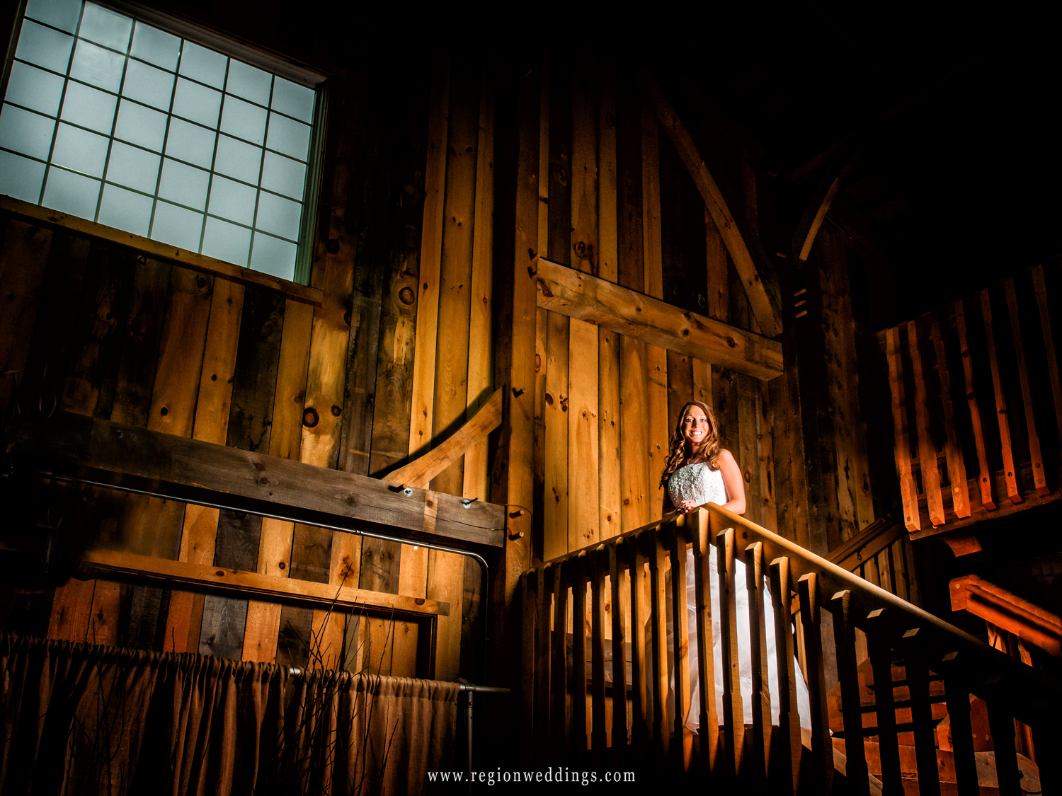 A bride stands alone on the staircase at County Line Orchard.