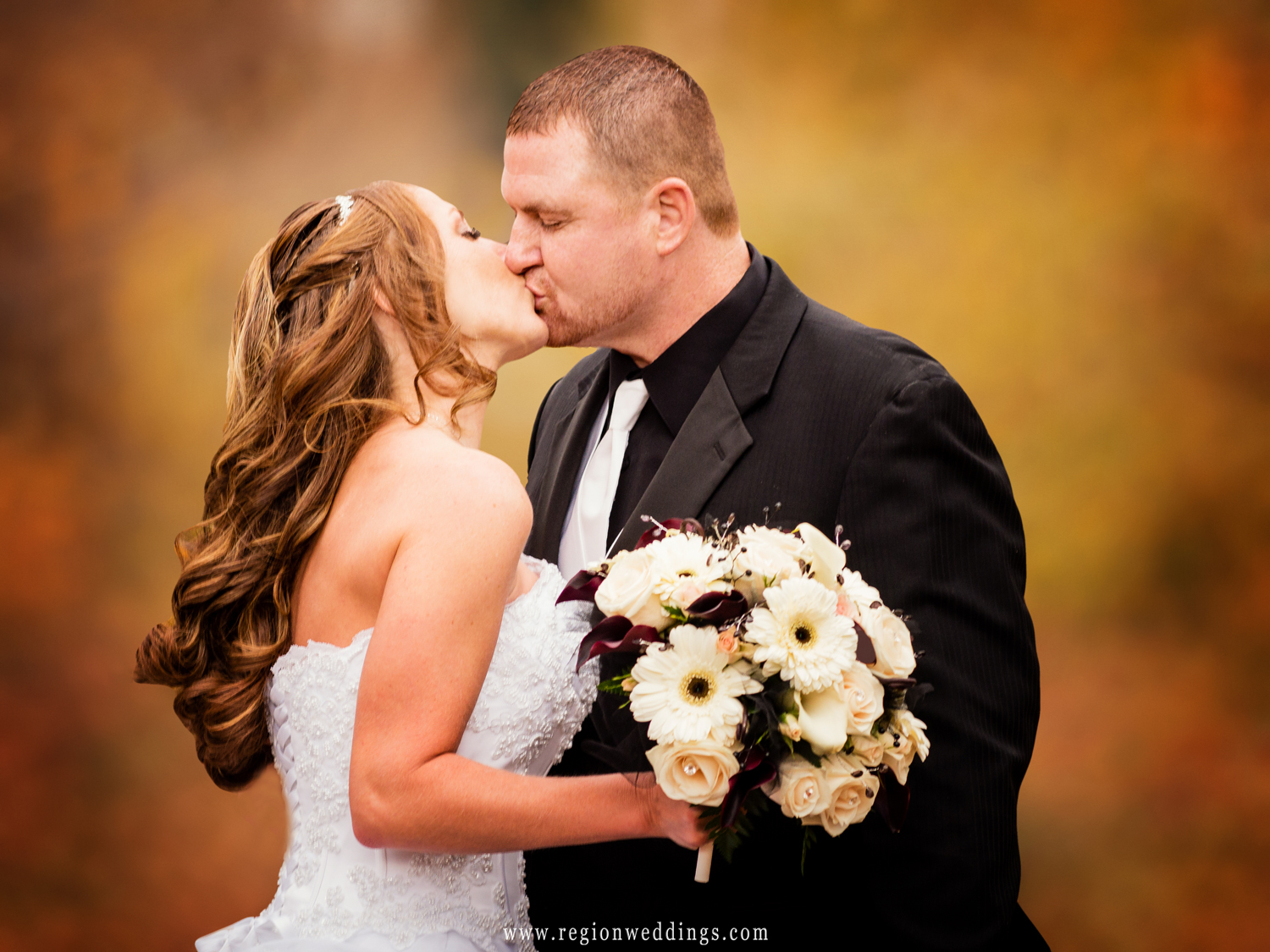 The bride and groom share a kiss amidst the Fall color of the apple fields at County Line Orchard.