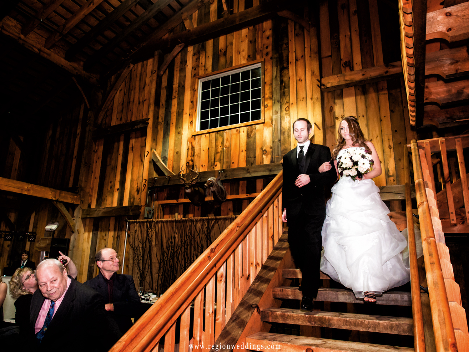 The bride is escorted down the rustic stair case by her brother during her winter wedding.