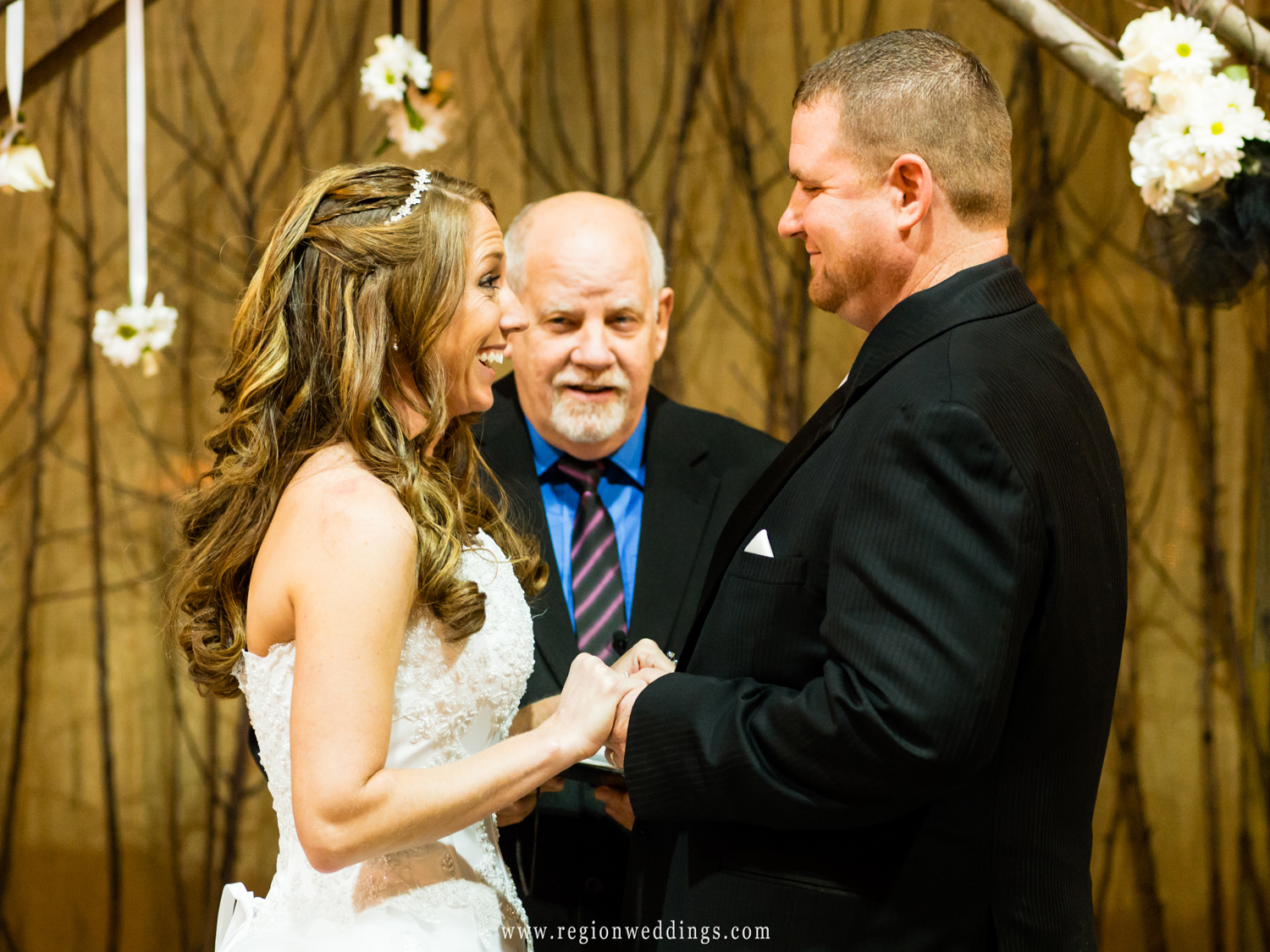 A couple exchanges vows during a wedding ceremony at County Line Orchard.