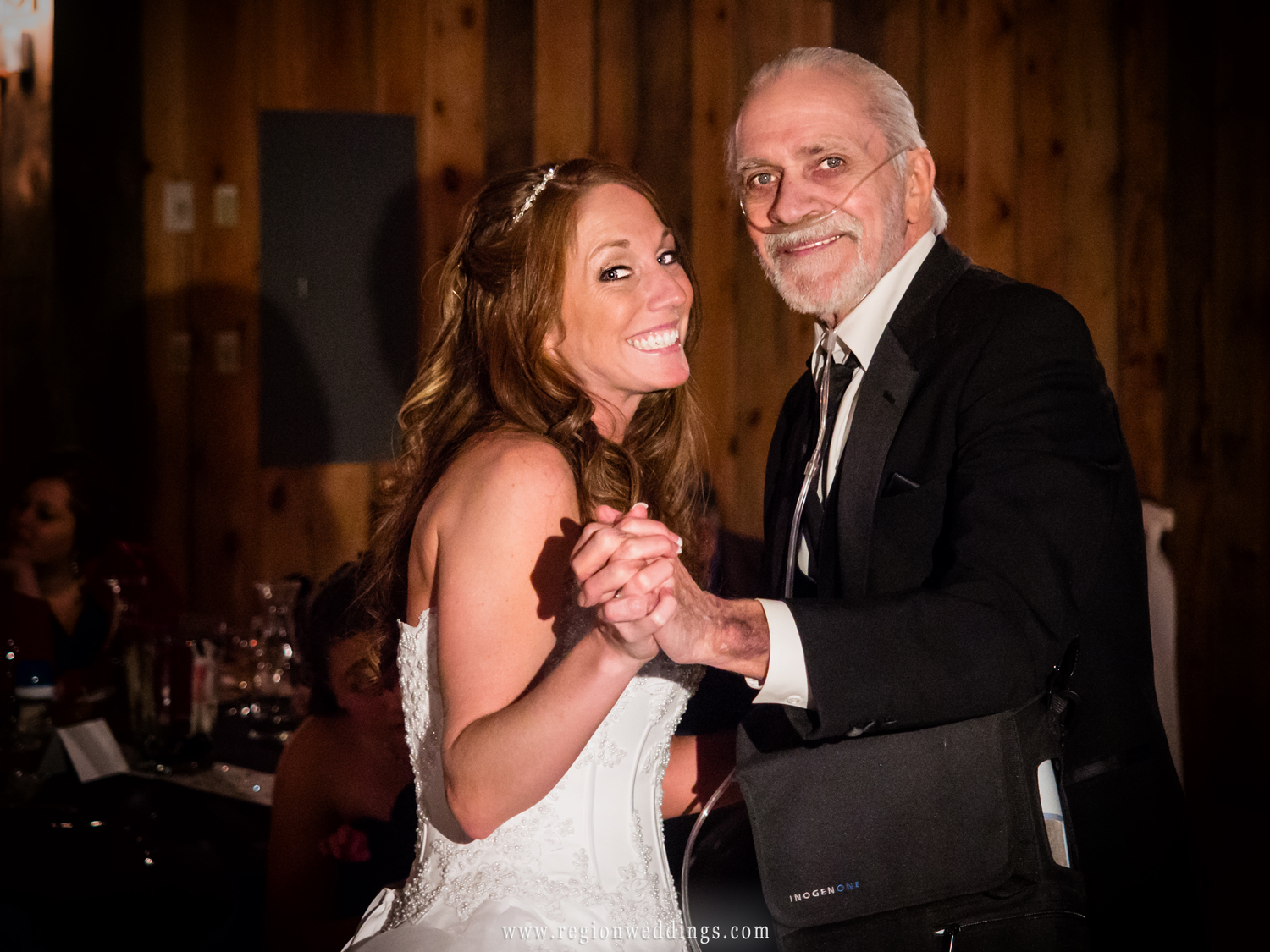 The bride dances with her father at a rustic barn wedding reception.