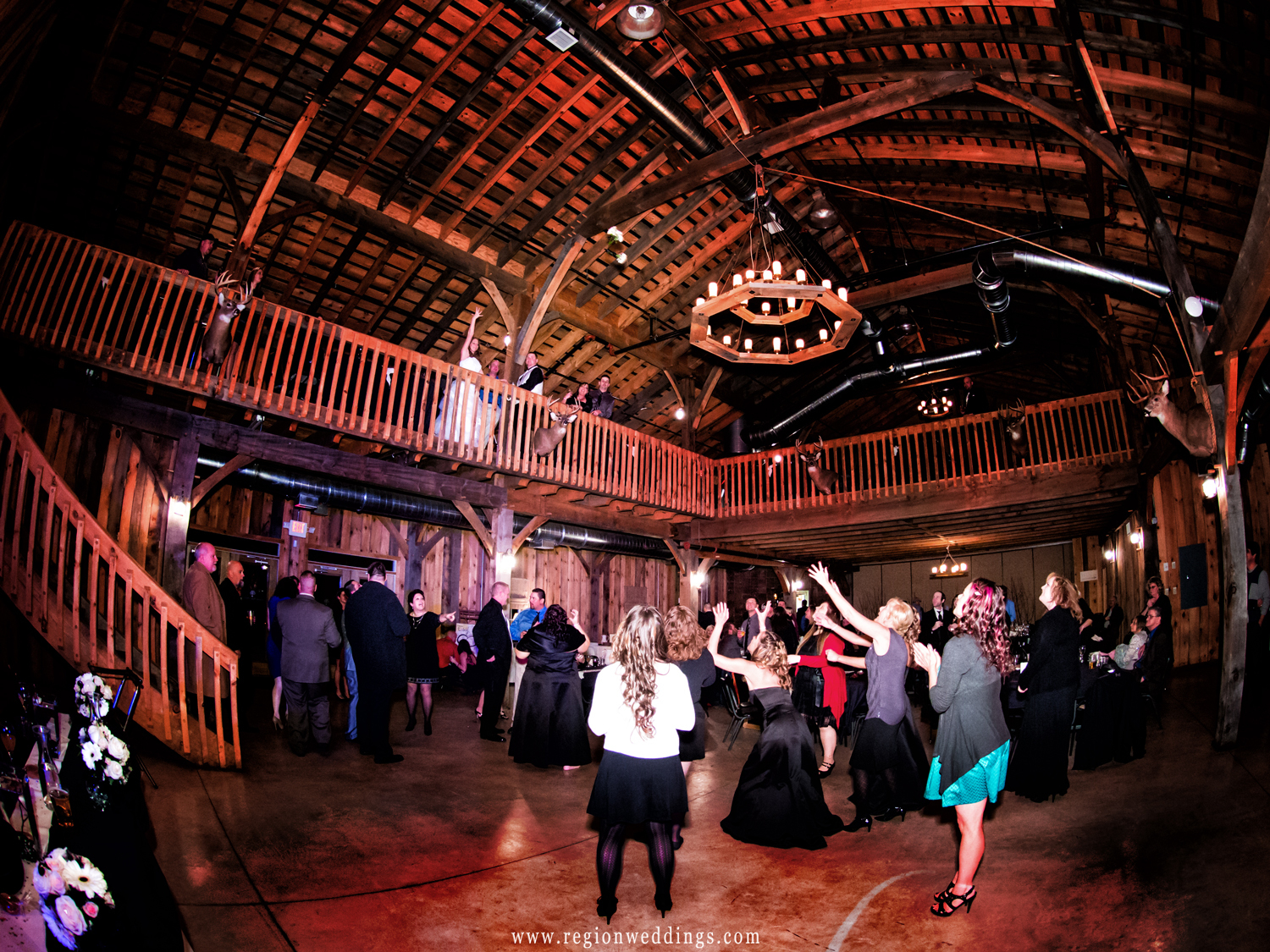 A crowd of women await on the dance floor as the bride tosses her bouquet from the balcony.