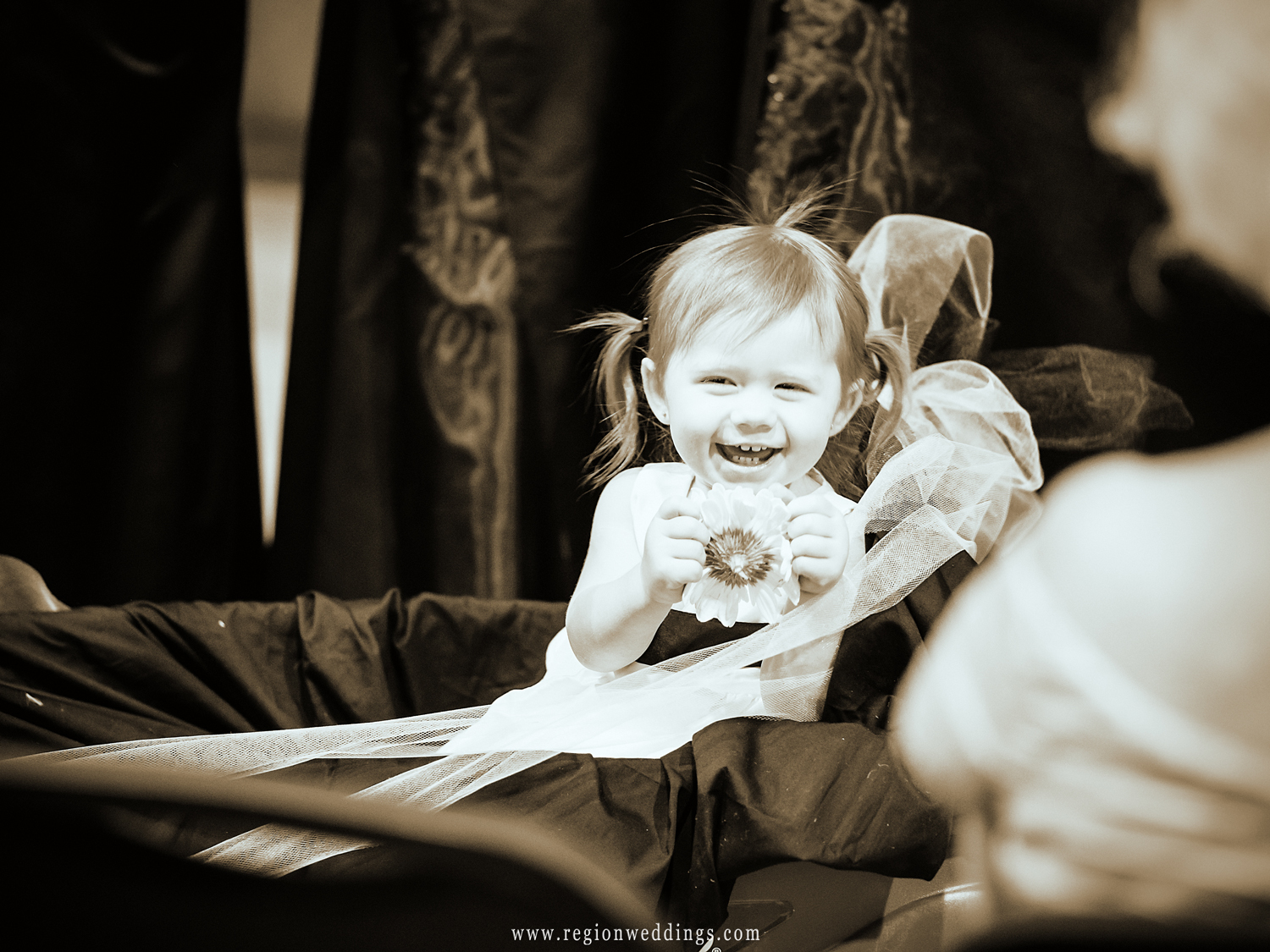 The flower girl enjoys the attention as she rides in via a red wagon.