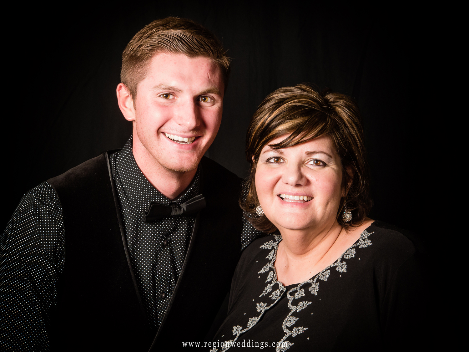 A mom poses with her son for a portrait against a black backdrop at a wedding reception banquet hall.