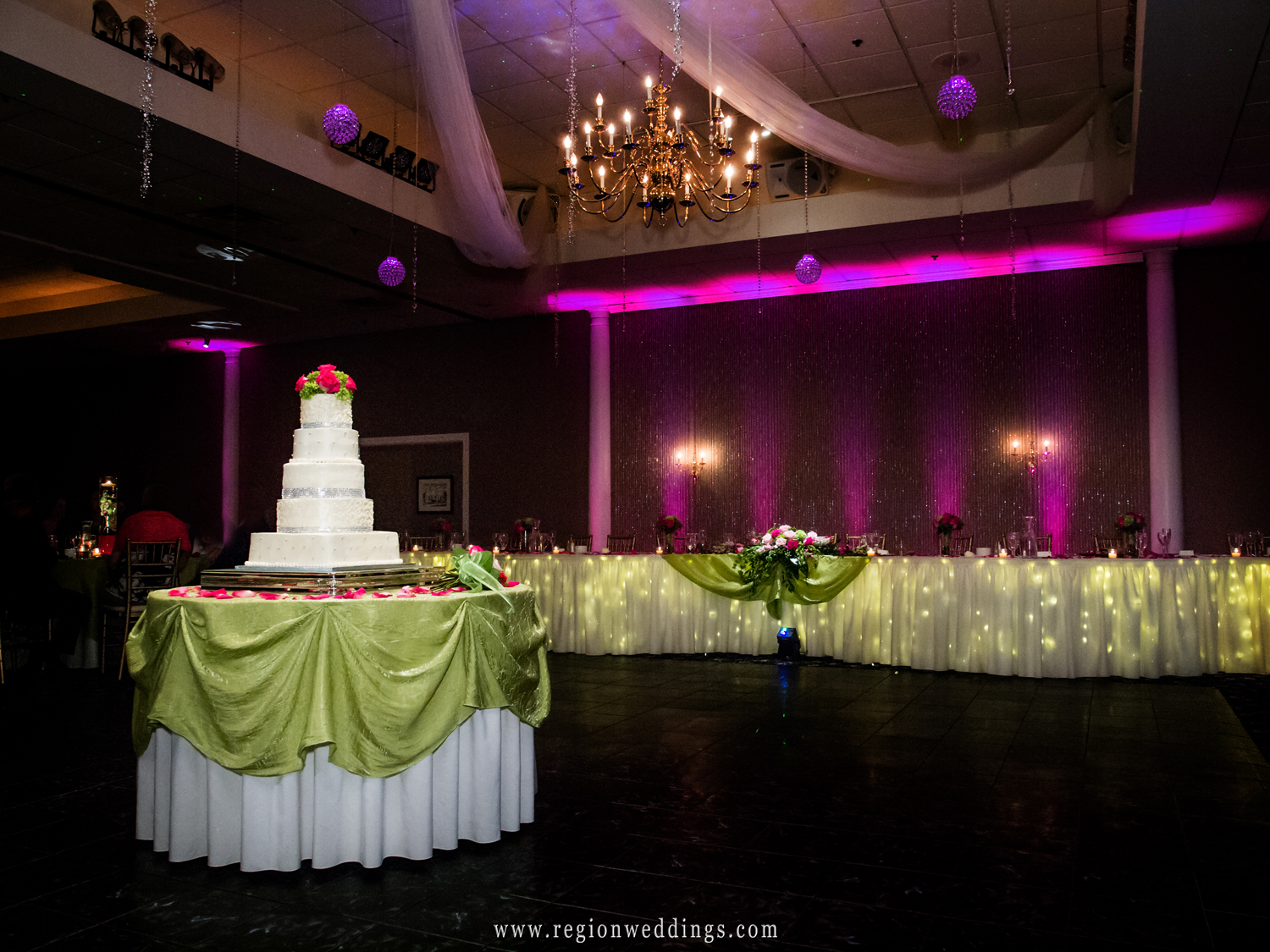 A gorgeous wedding cake with a pink topper sits inside the ballroom at Aberdeen Manor in Valparaiso, Indiana.
