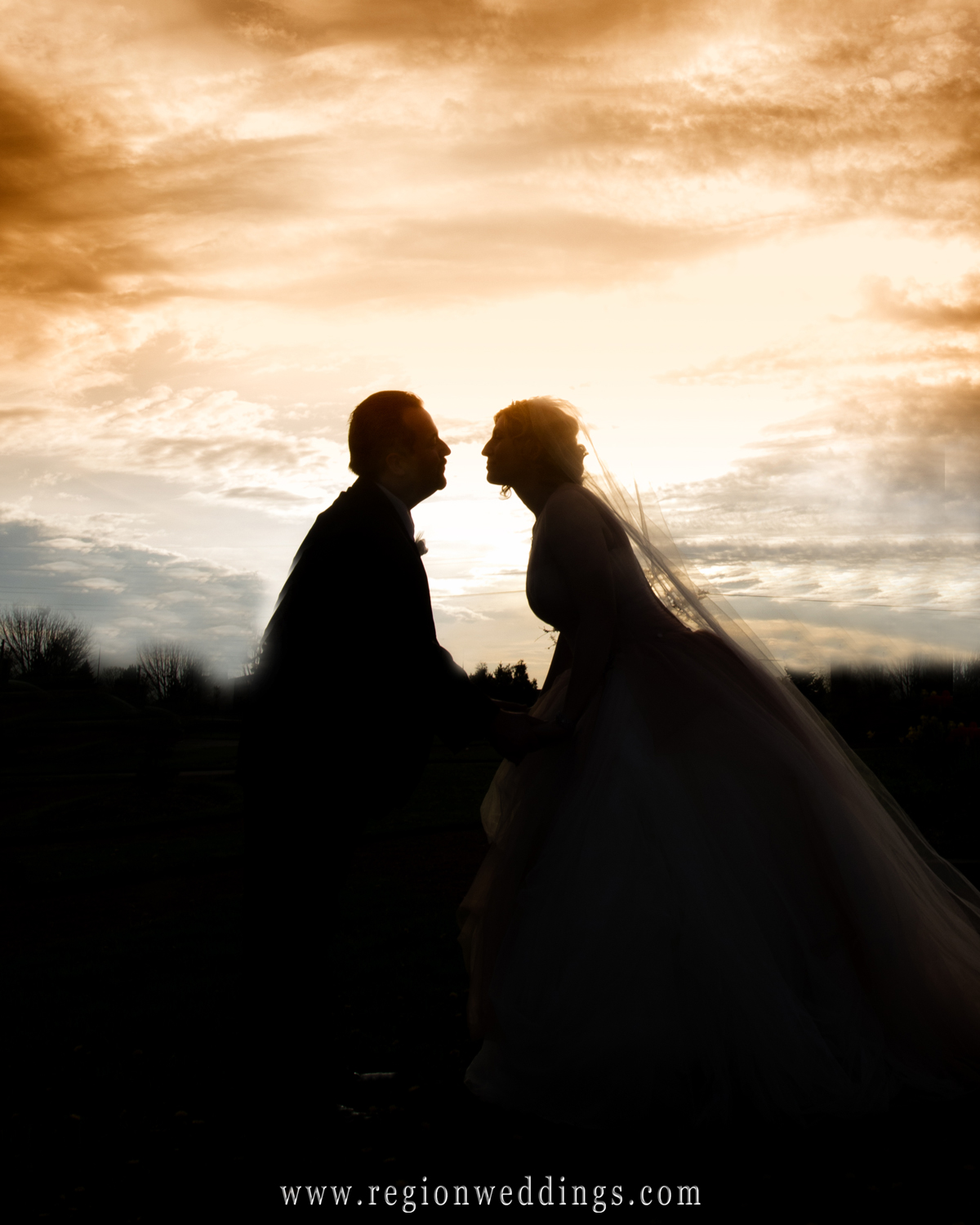 Silhouette of the bride and groom about to kiss on a warm Spring night with the sun setting in the background.