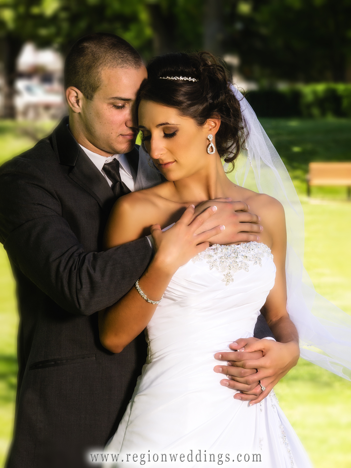 A romantic embrace between bride and groom after their summer wedding ceremony.