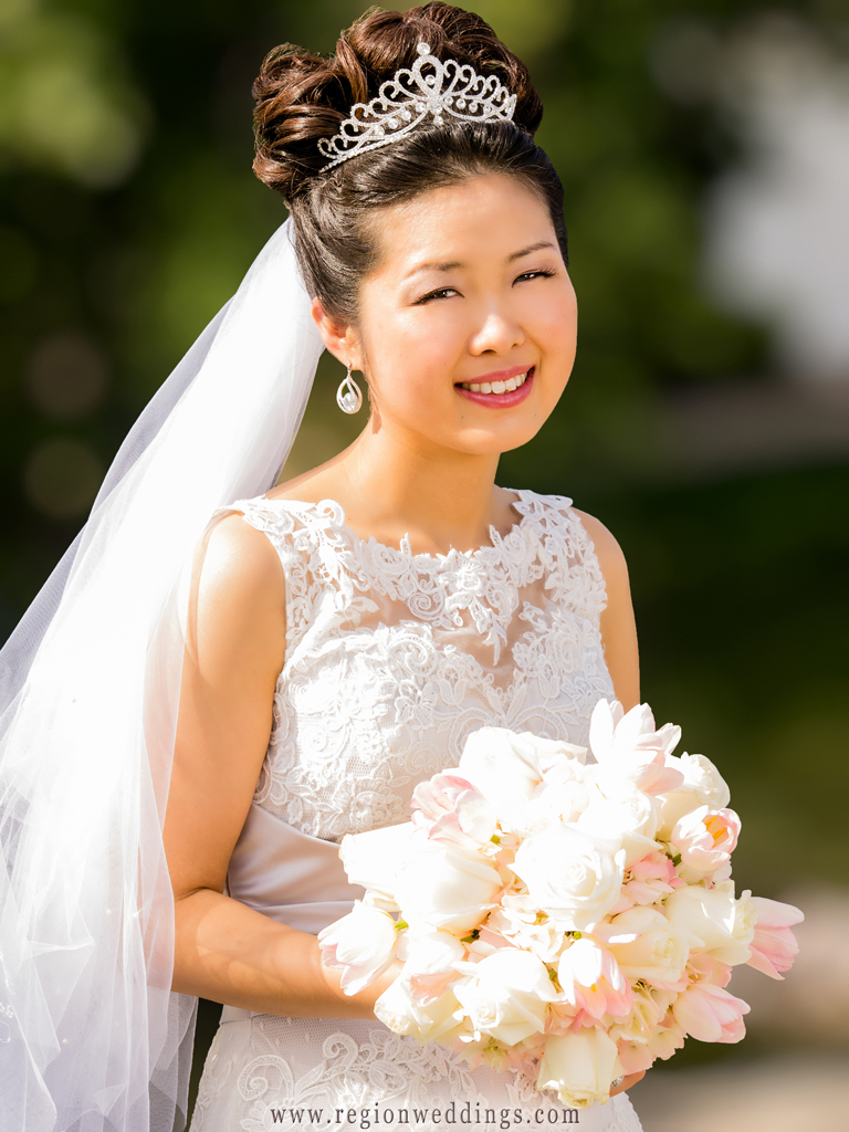 Korean bride wearing a tiara poses in her wedding dress on a beautiful summer day.