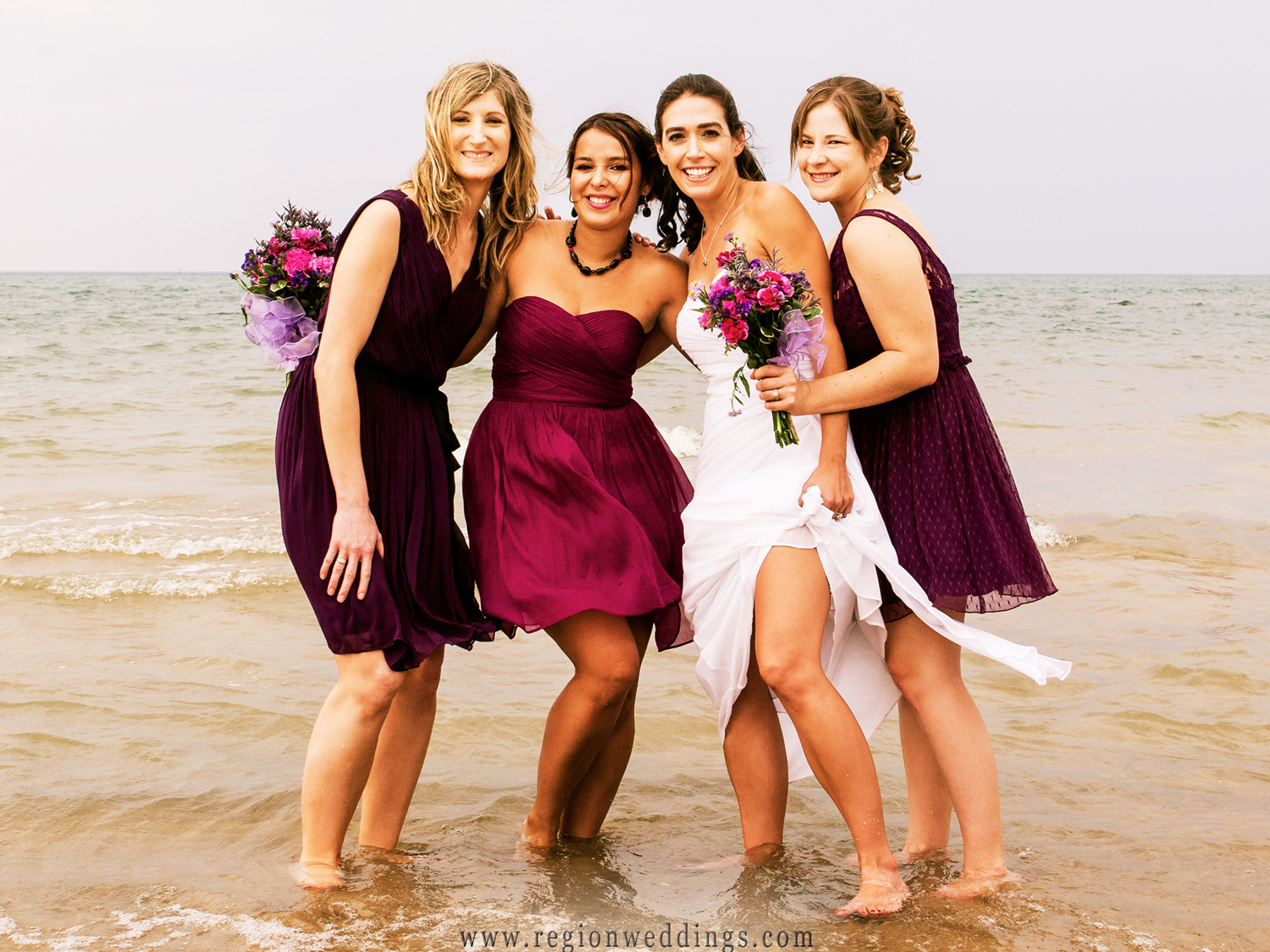 Bridesmaids step into Lake Michigan in their dresses for a wedding photo.