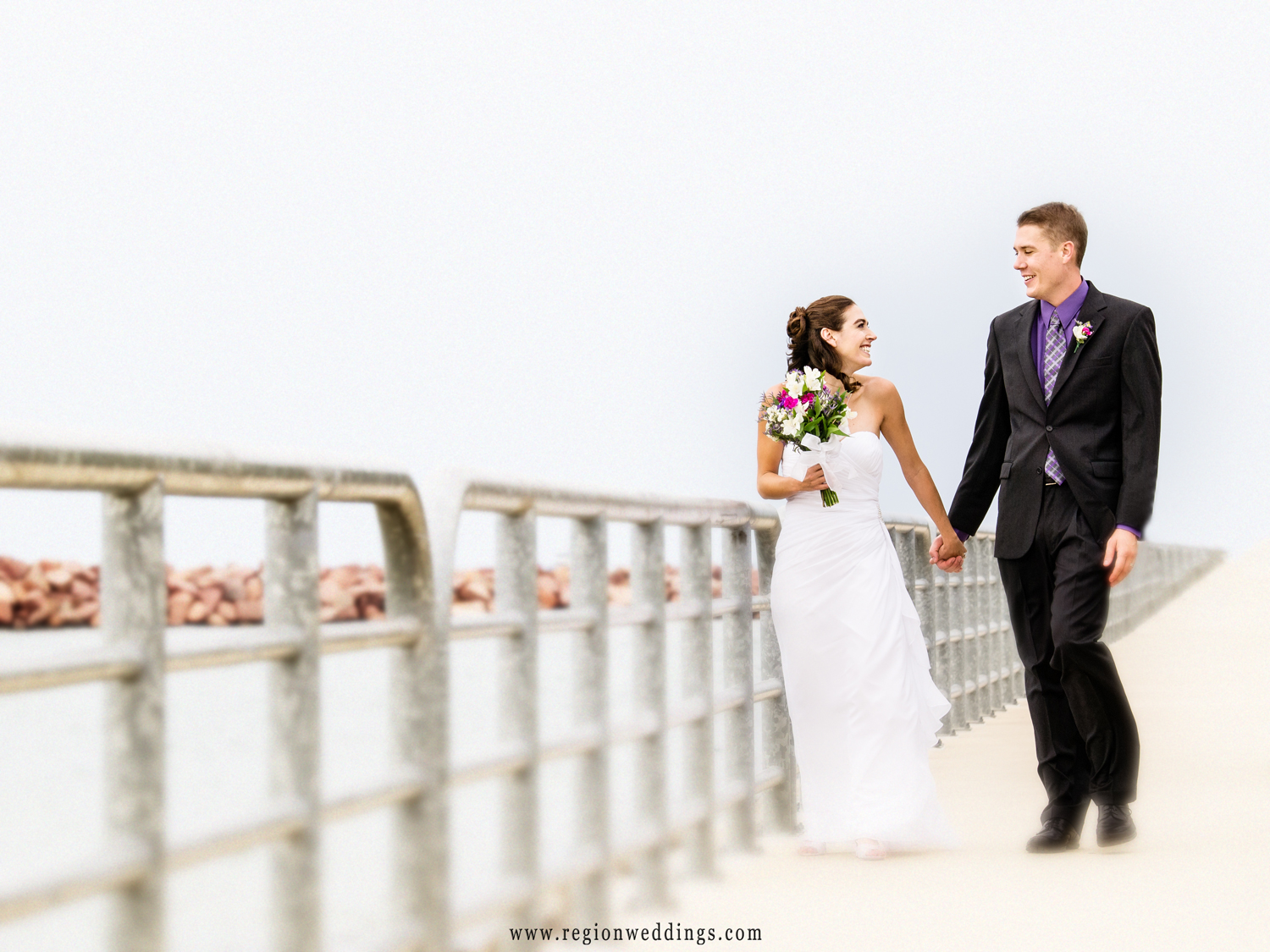 A newly married couple walks along the beach at Indiana Dunes.