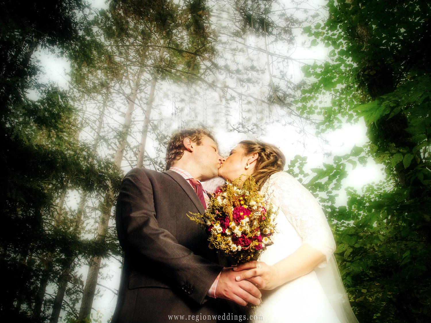 The bride and groom kiss amidst the forest trees in Michigan during the Fall season.