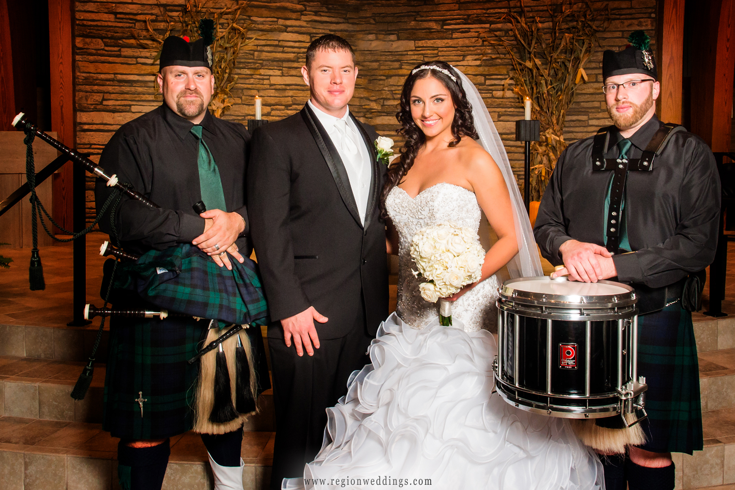 Bag pipe players pose with the bride and groom after their wedding ceremony at Our Lady of Grace Church.