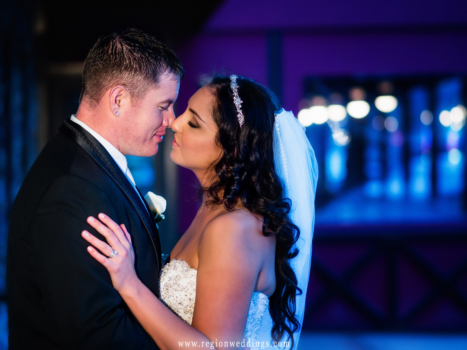 A night time wedding photo in downtown Highland with the bride and groom snuggling close.