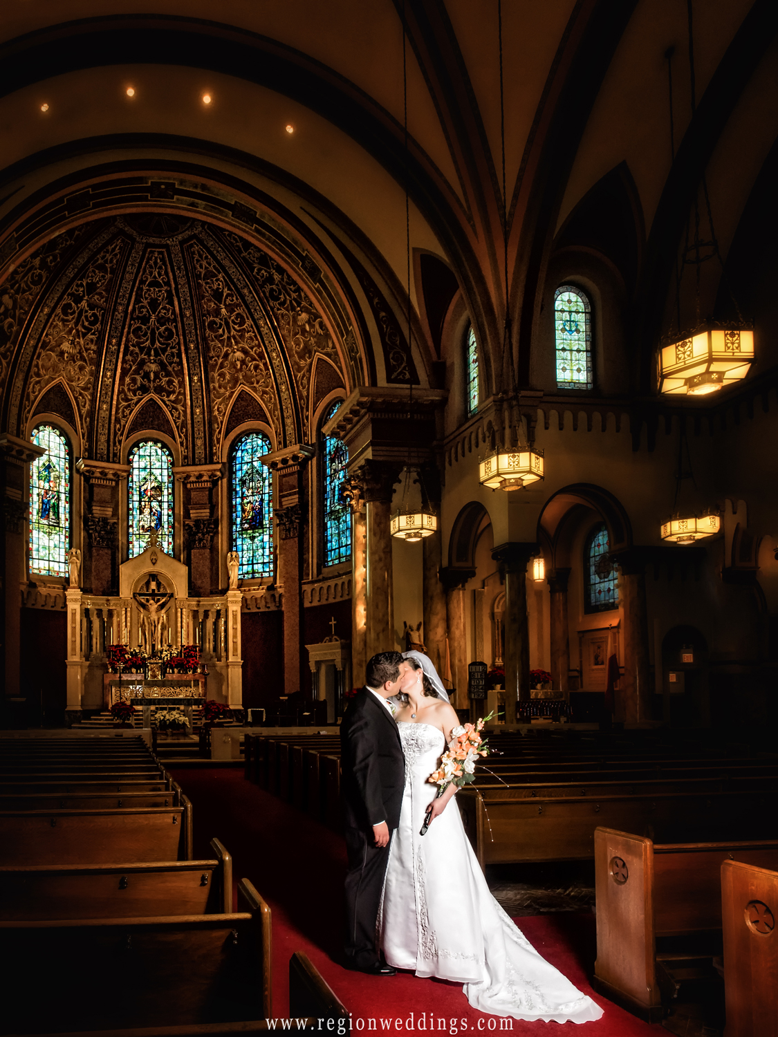 Bride and groom kiss in the aisle of the spectacular Saint Andrew the Apostle Parish in Calumet City.