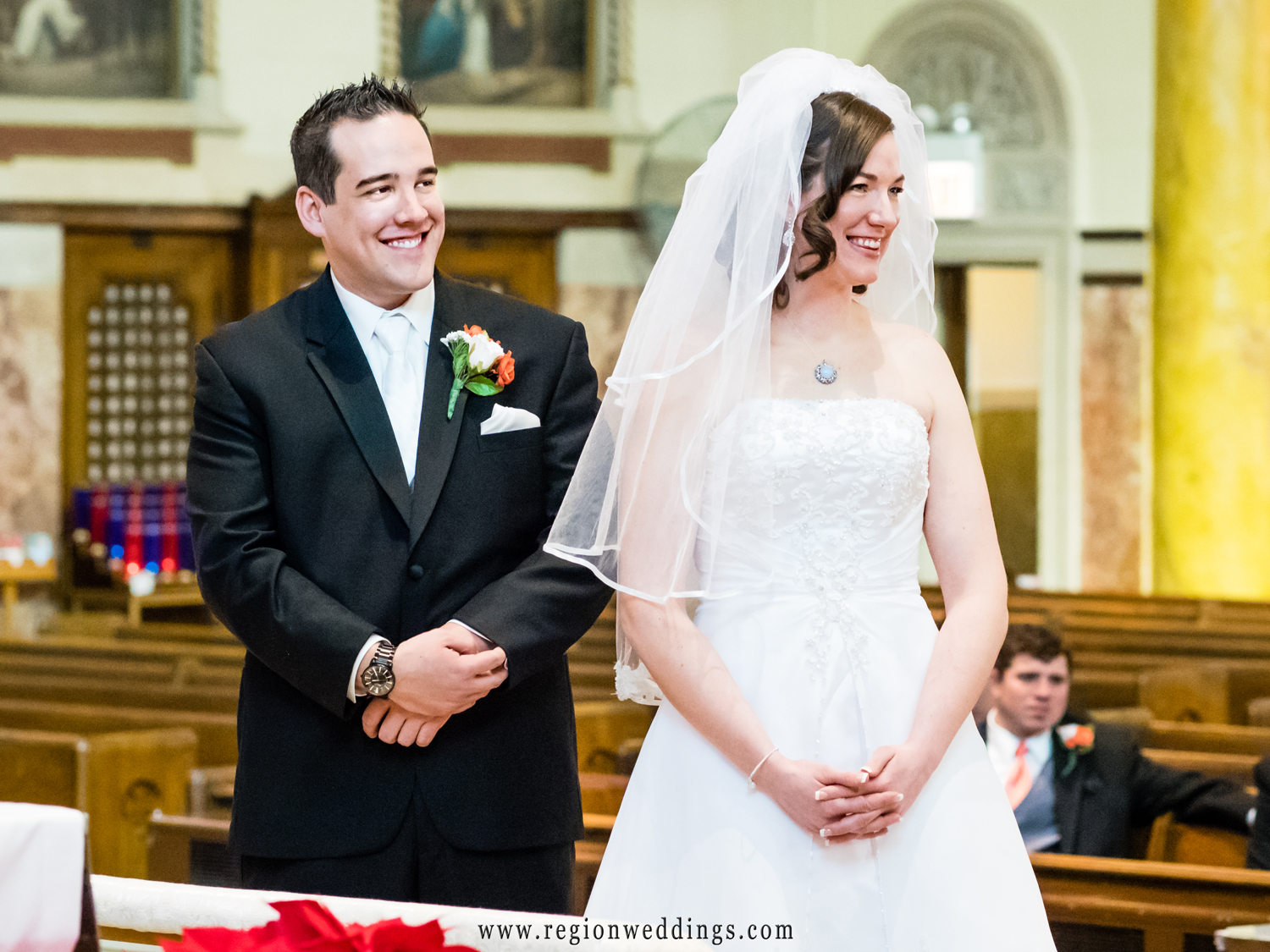 The couple reacts with smiles as their priest performs their Catholic wedding ceremony.