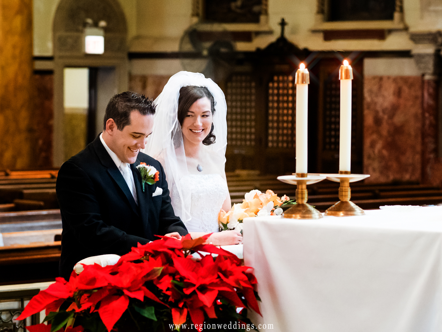 A candid moment between the bride and groom at the altar of Saint Andrew the Apostle Parish.