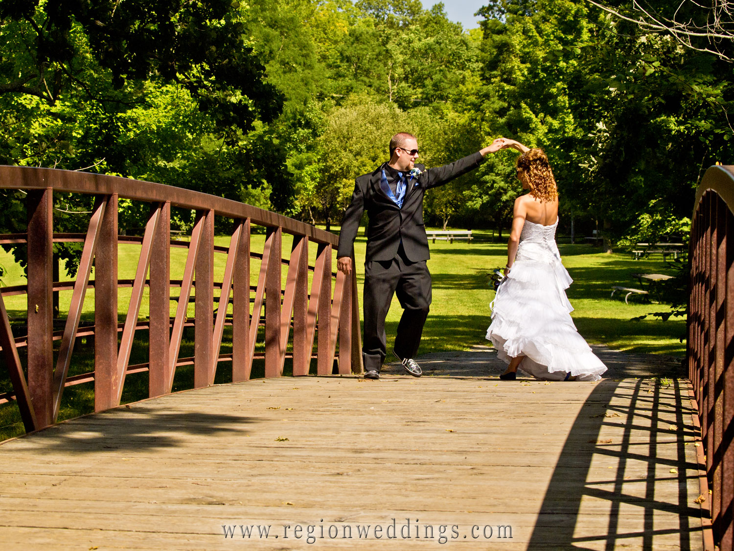 Bride and groom dance their way across the bridge at Deep River County Park.