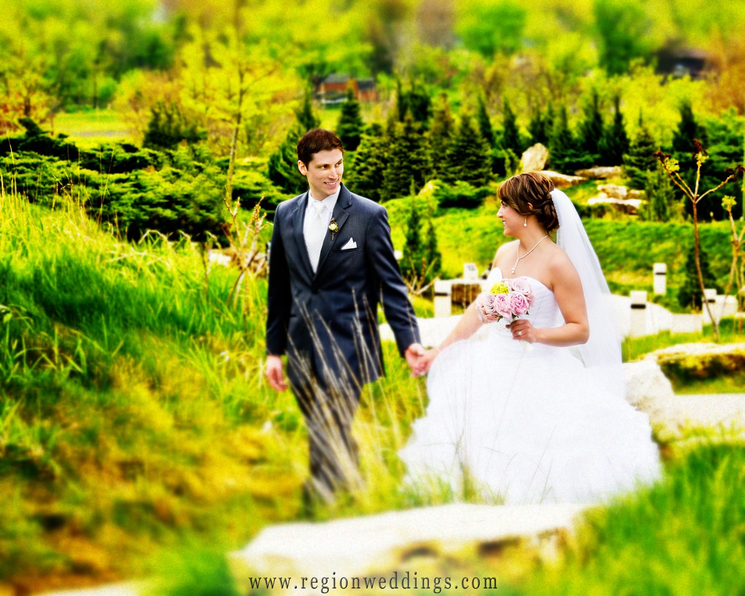 Newly married couple walks among the greenery at The Shrine of Christ's Passion in Saint John, Indiana.
