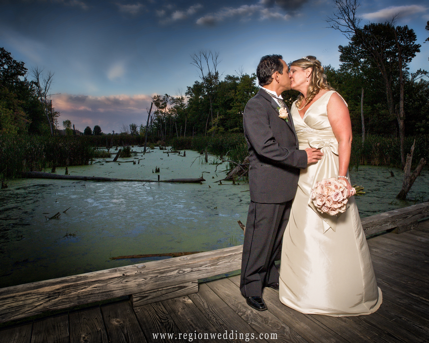 A couple kisses on a bridge that overlooks an exotic swamp at White Hawk Country Club in Crown Point, Indiana.