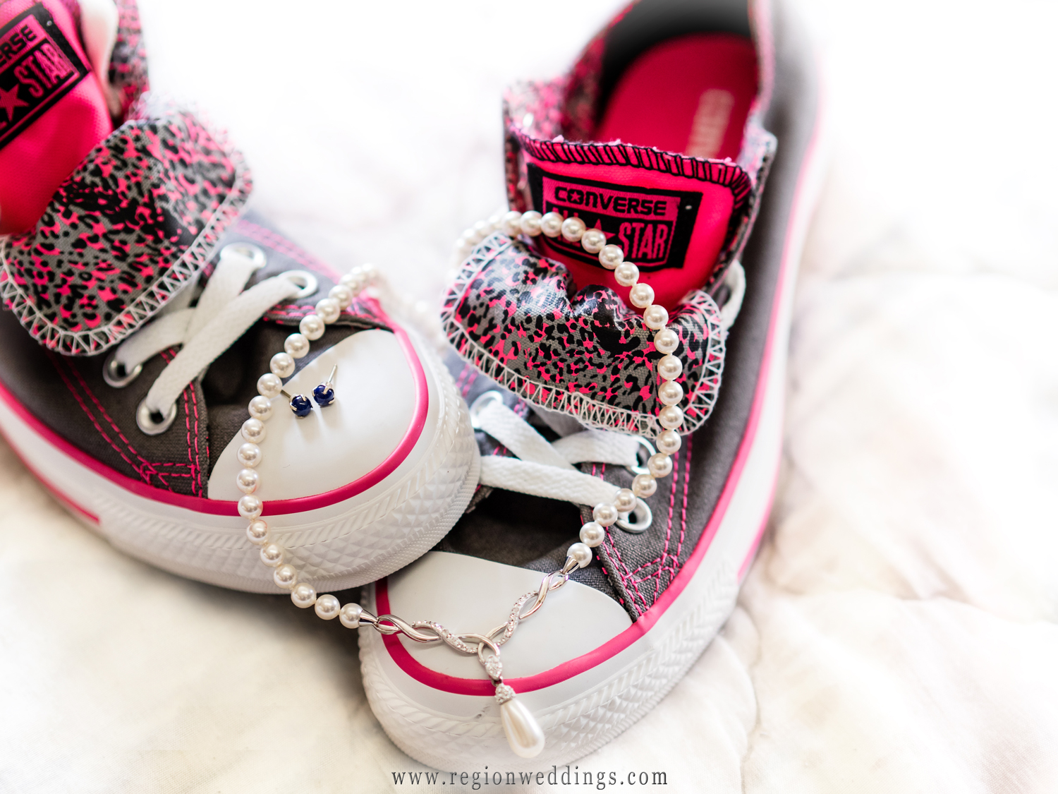 The bride's shoes are pink Converse All Star sneakers decorated with her wedding jewelry.