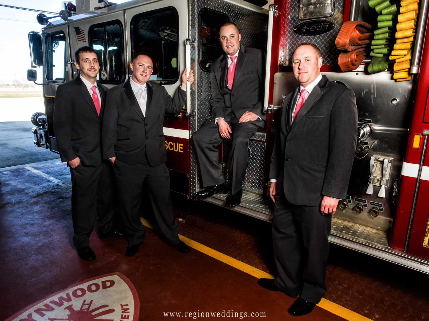A group of fireman on their friends wedding day in front of a fire truck at the Lynwood station.