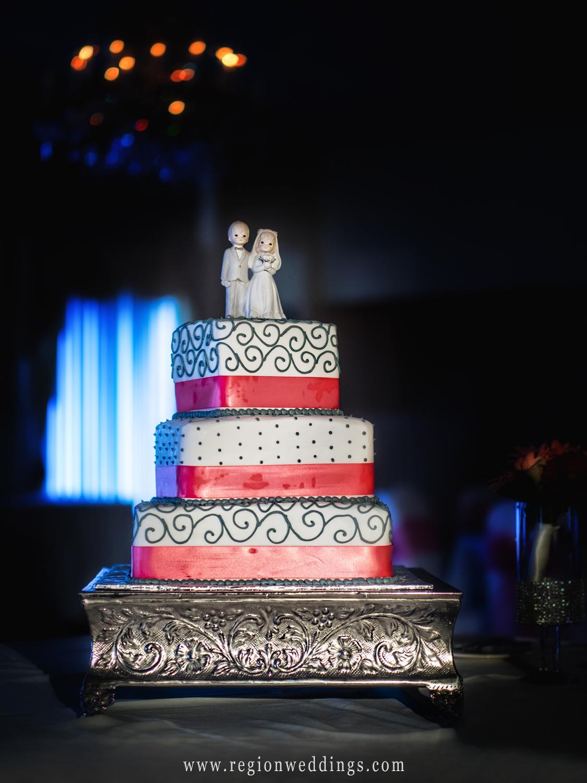 Three tier wedding cake with pink trim.