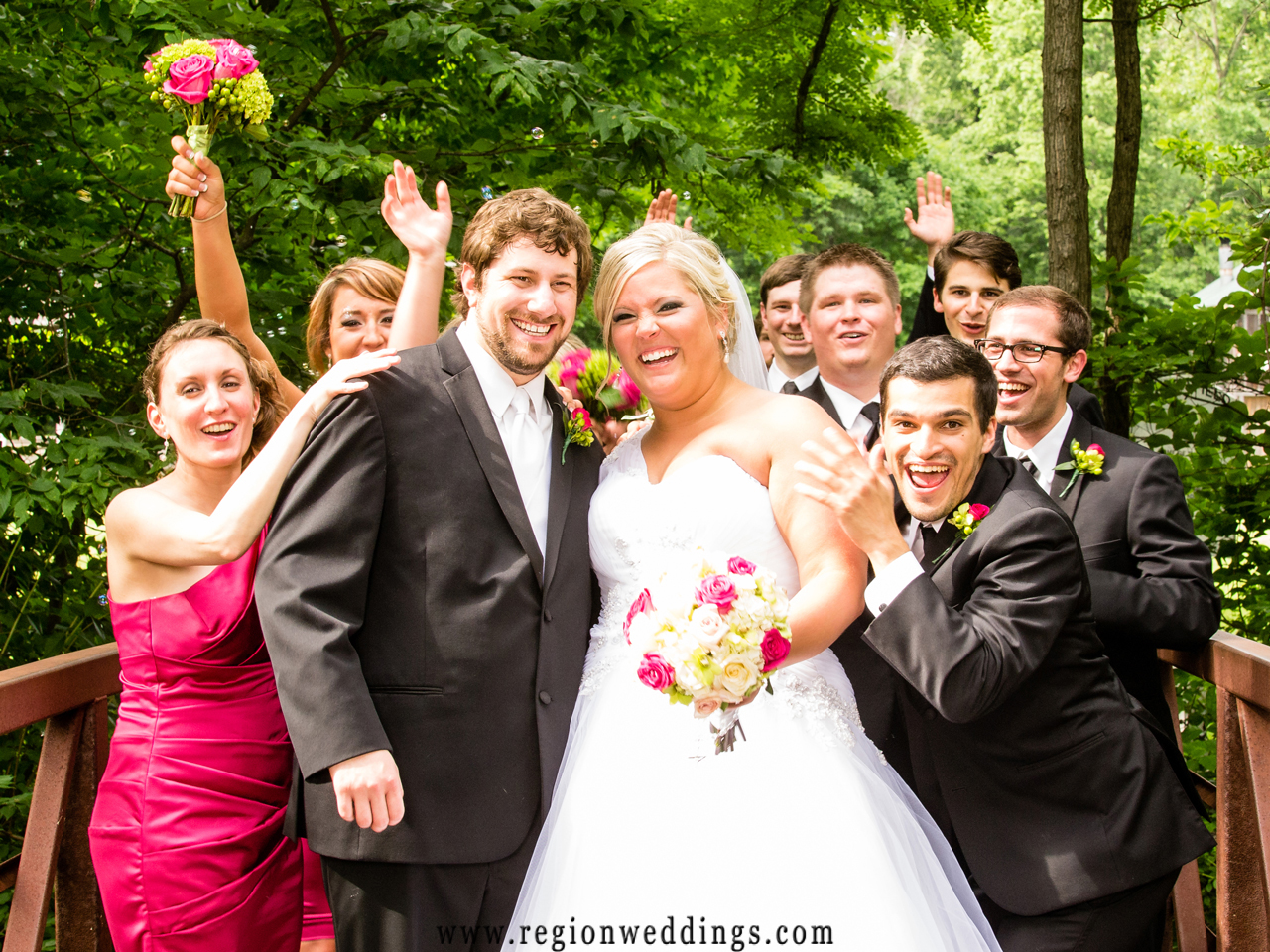 A happy wedding party whoops it up on the bridge at Deep River County Park.
