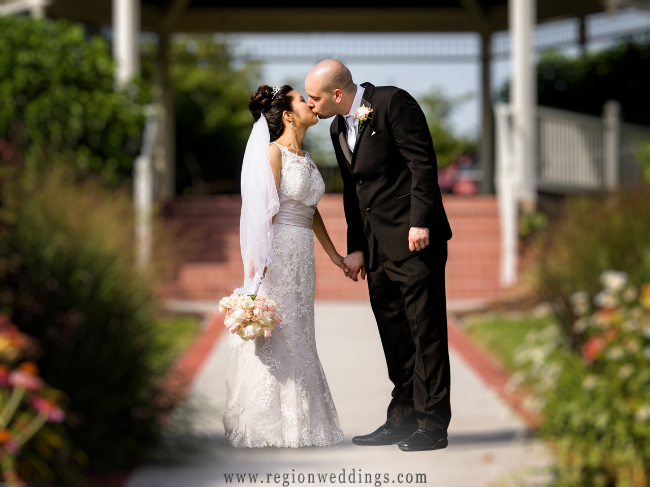 A newly married couple kiss in front of the gazebo at Ellendale Farms in Crown Point, Indiana.