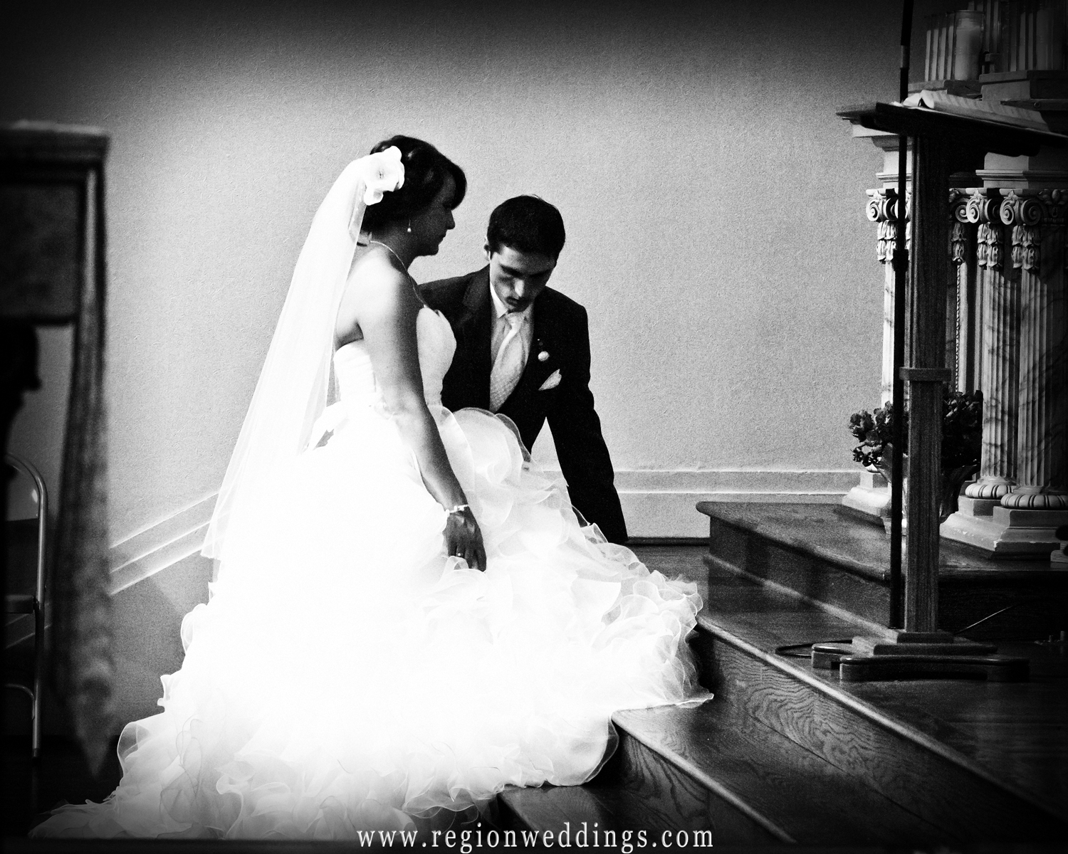 The groom helps the bride up from kneeling during their wedding ceremony at St. John the Evangelist Church.