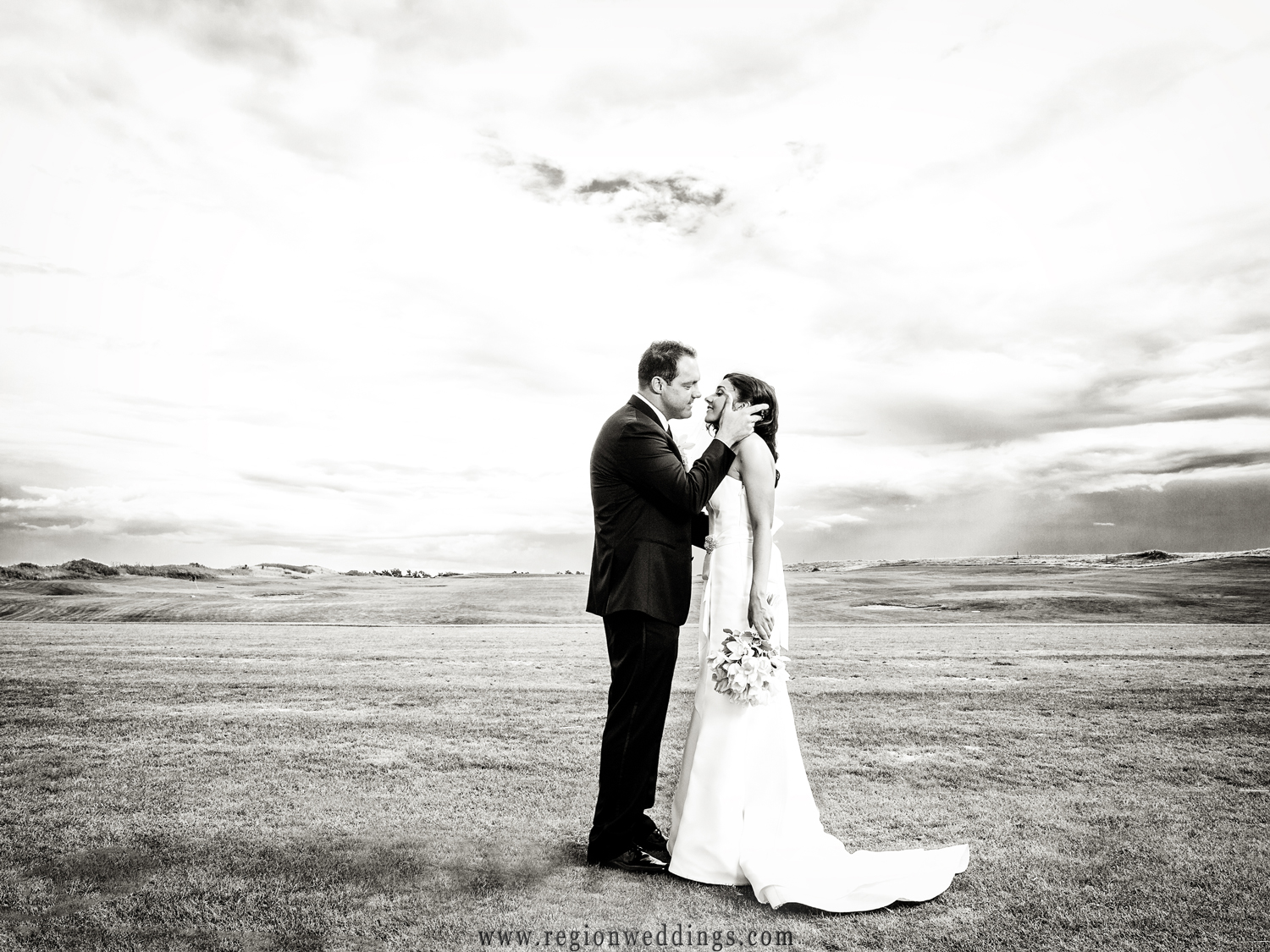 The groom is about to kiss his new bride in this romantic black and white wedding photo.