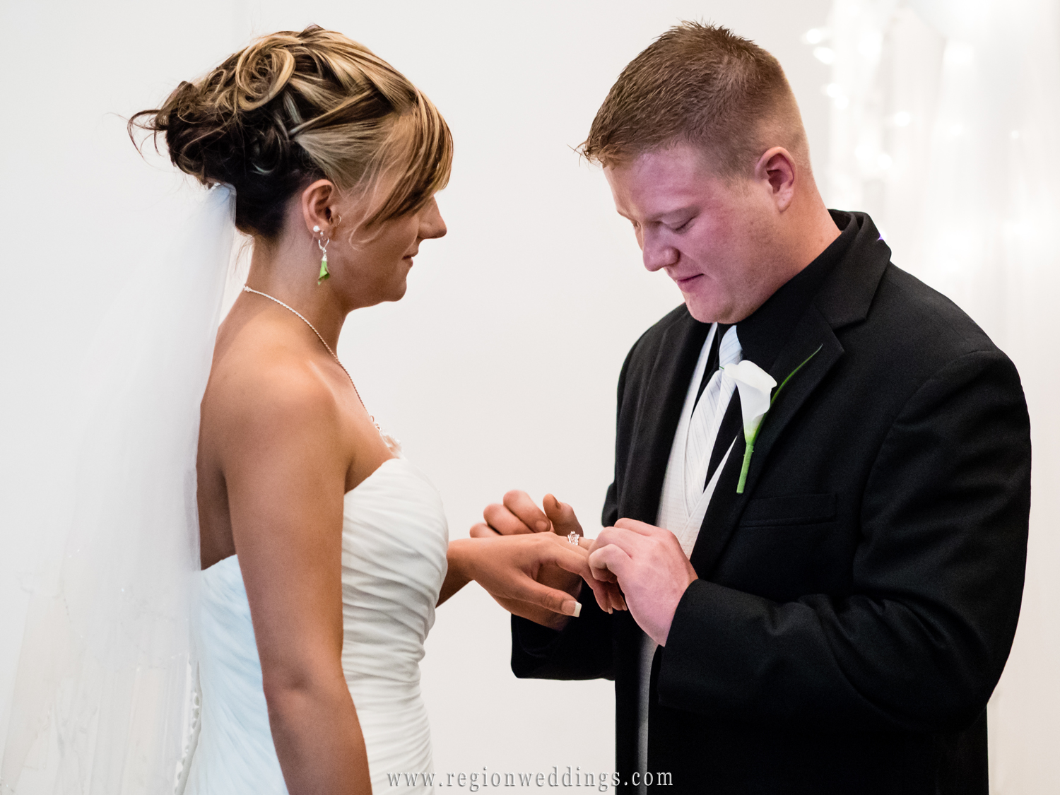 The groom places the ring on his bride's finger at an indoor ceremony at The Patrician.