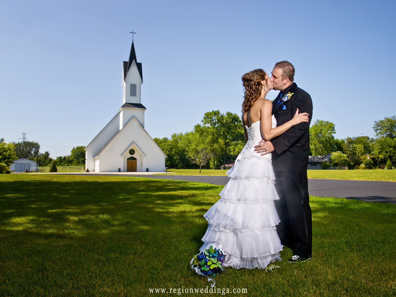 Bride and groom kiss at the entrance to Grace Lutheran Church in Hobart, Indiana.