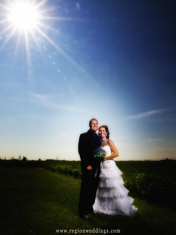 The bride and groom underneath a summer sunburst at an Indiana farm on their wedding day.