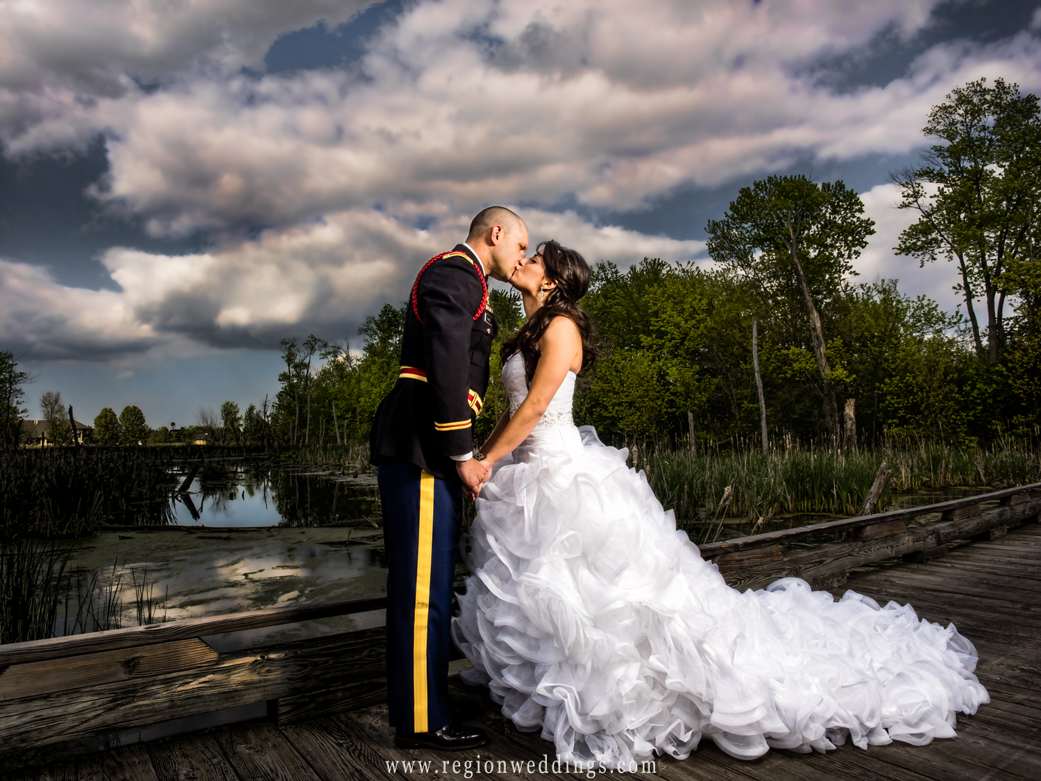 The bride and groom share a kiss on the scenic bridge at White Hawk Country Club in Crown Point, Indiana.