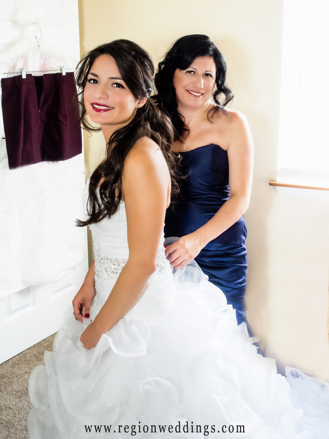 The mother of the bride laces up her dress on wedding day.