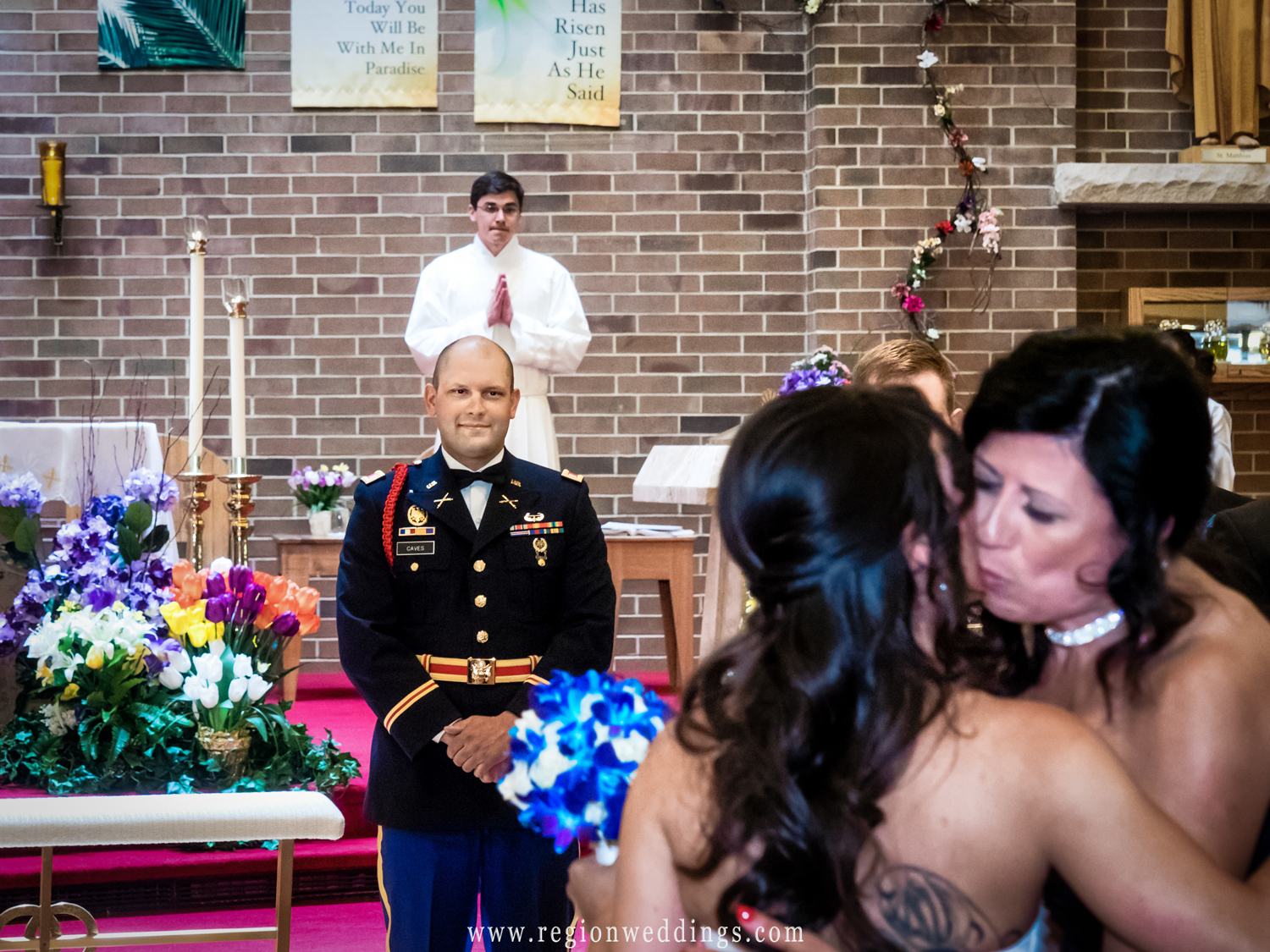 The groom smiles broadly as his bride's mother gives her away during their military wedding at Saint Matthias.