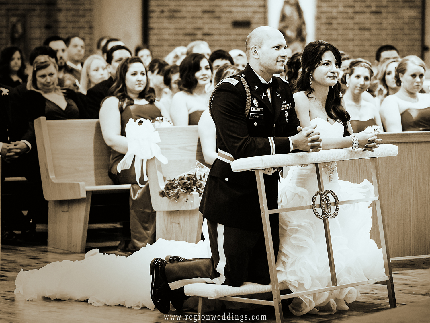 The bride and groom listen to father while kneeling on pews during their wedding ceremony at St. Matthias Church.