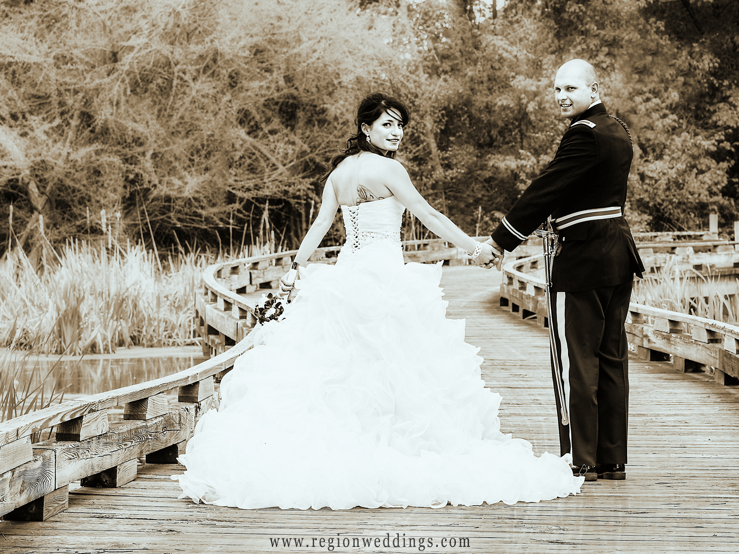 The newly married couple takes a stroll across the bridge at White Hawk Country Club in Crown Point.