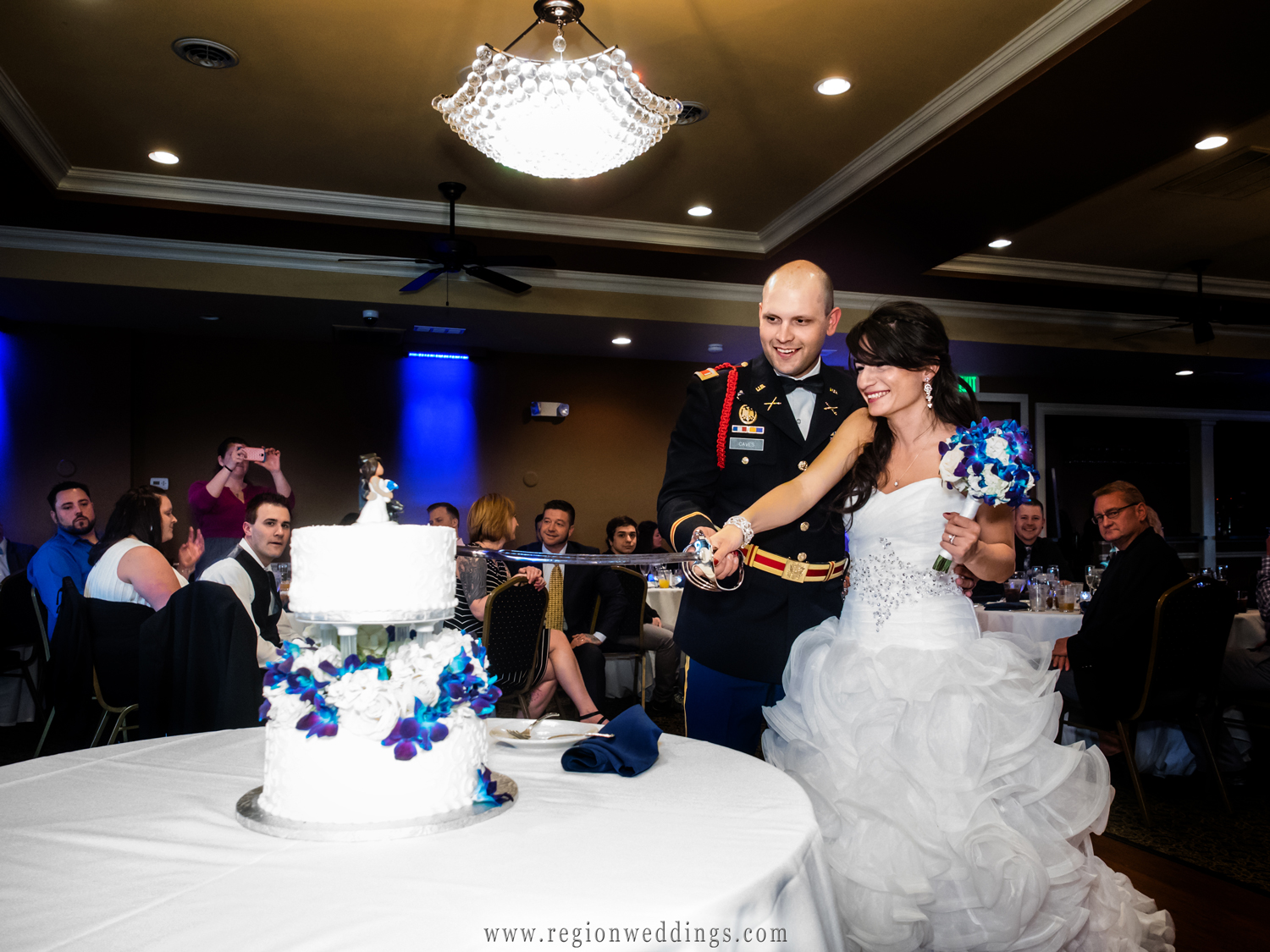 The bride and groom cut their cake with a sword.