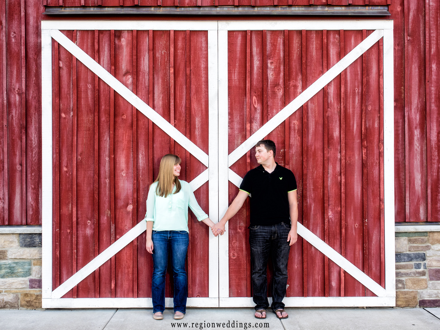 Engagement photo in front of the red barn doors at County Line Orchard.