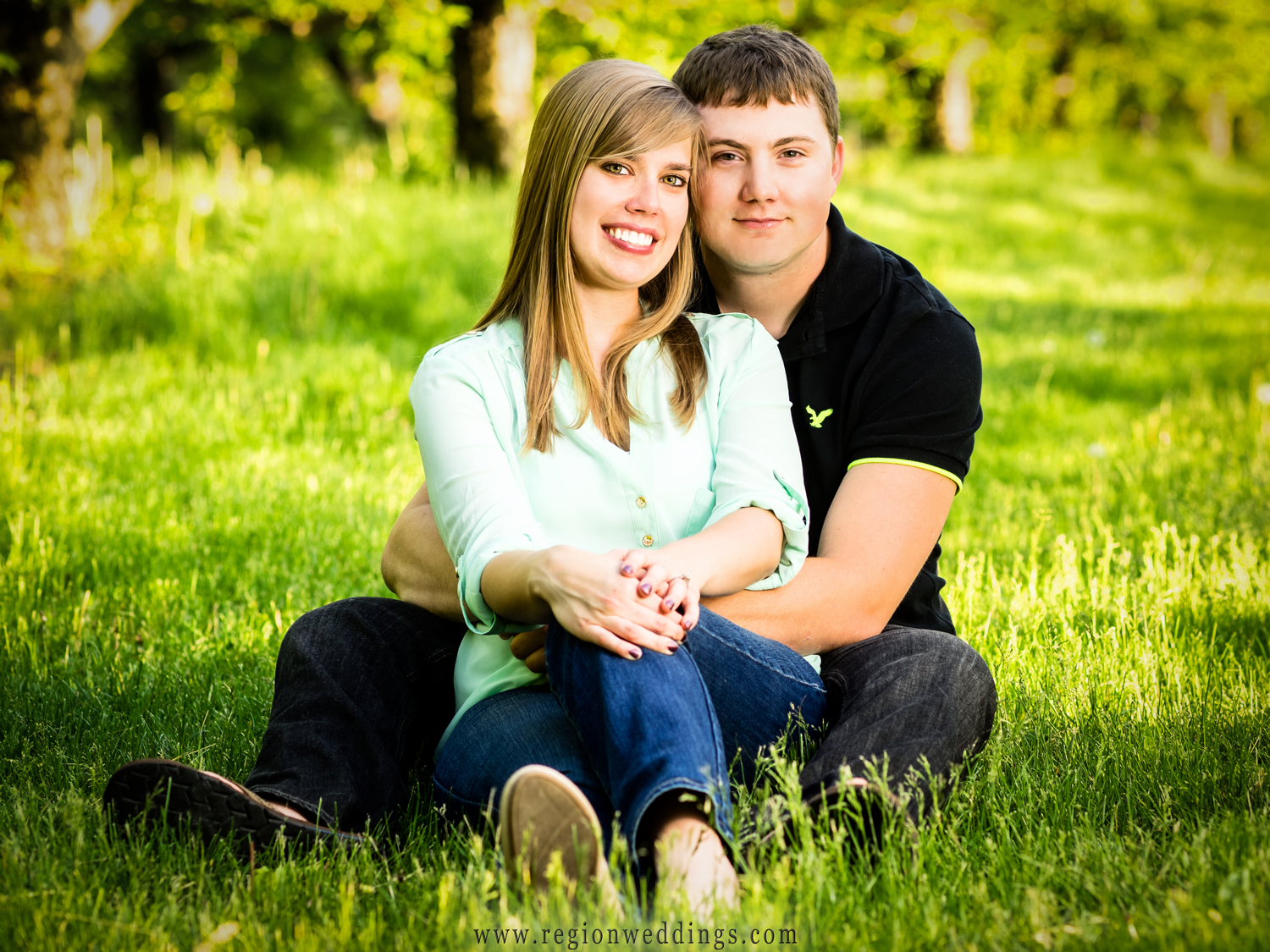 Portrait of a soon to be married couple in the grass at the apple orchards in Hobart, Indiana.