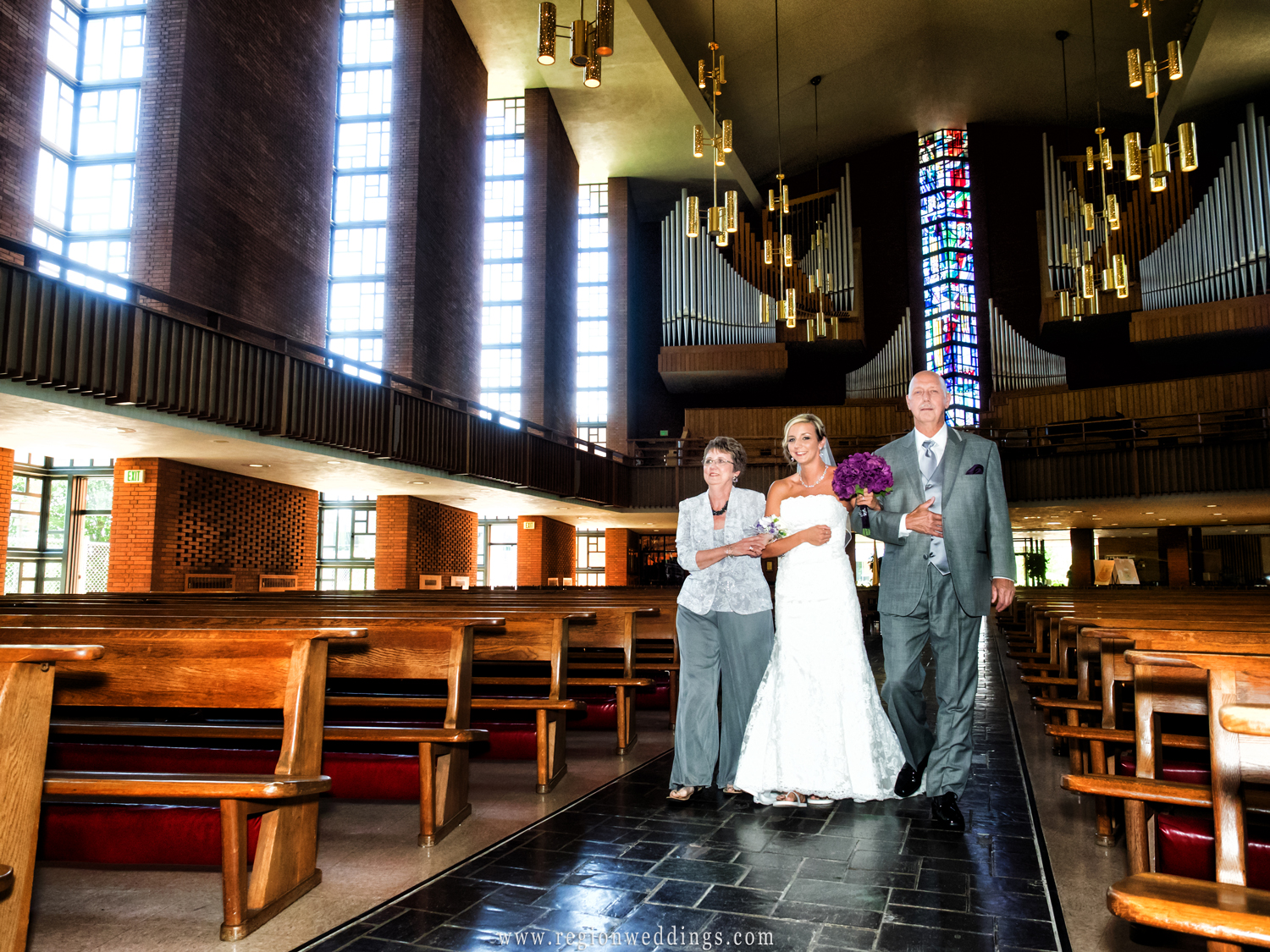 The bride is accompanied by her parents as she walks down the aisle at The Chapel of the Resurrection.