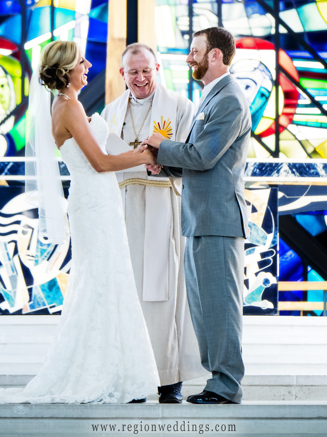 The bride and groom share a laugh with their pastor during their wedding ceremony at The Chapel of the Resurrection.