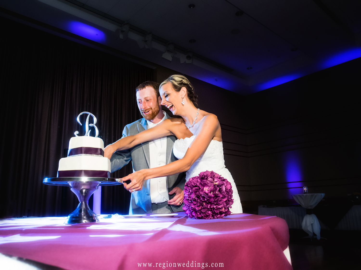 The bride and groom cut their plum colored wedding cake.