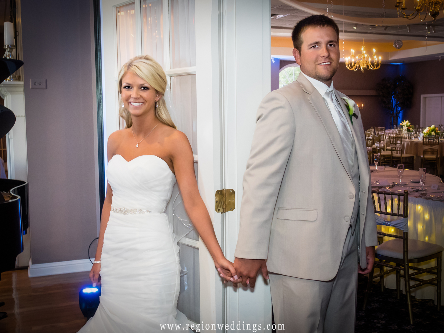 The bride and groom hold hands as they stand at opposite sides of a doorway.