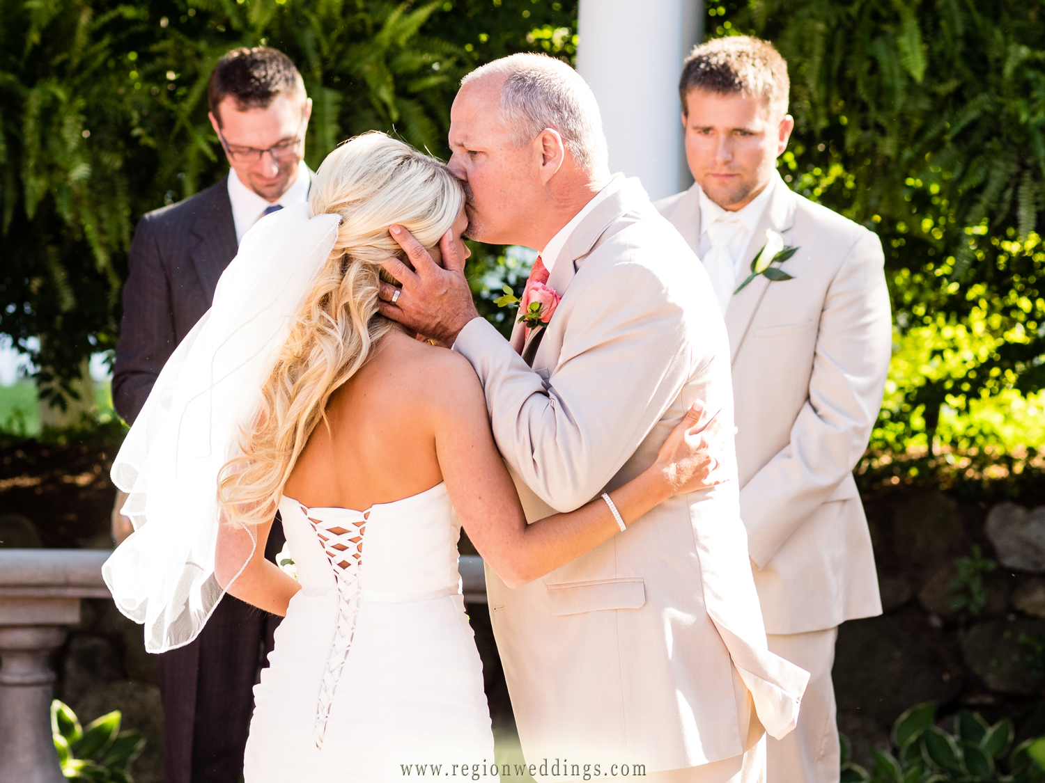 The bride's father kisses her before giving her away.