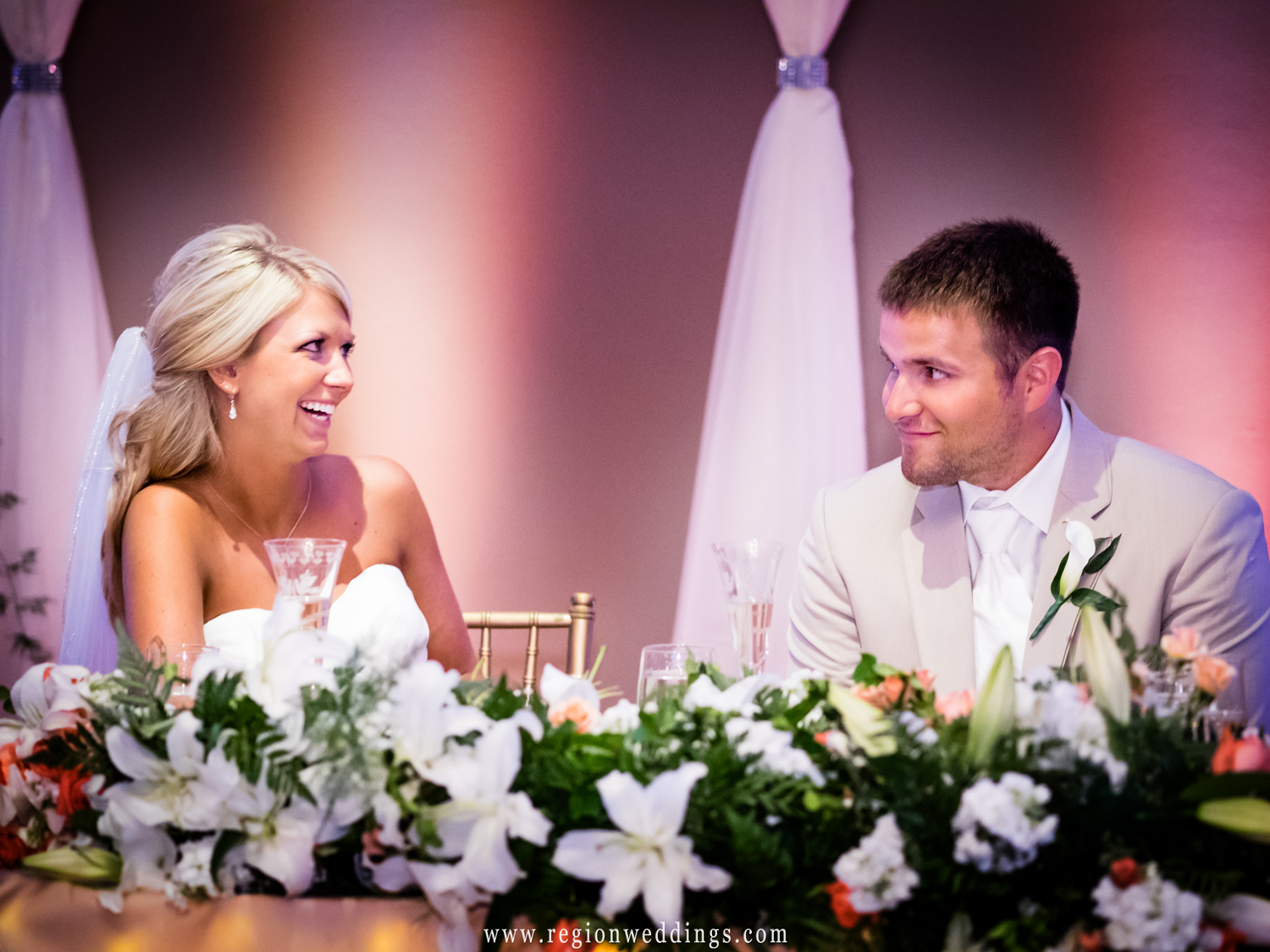 The bride and groom share a knowing look at their wedding reception at Aberdeen Manor.