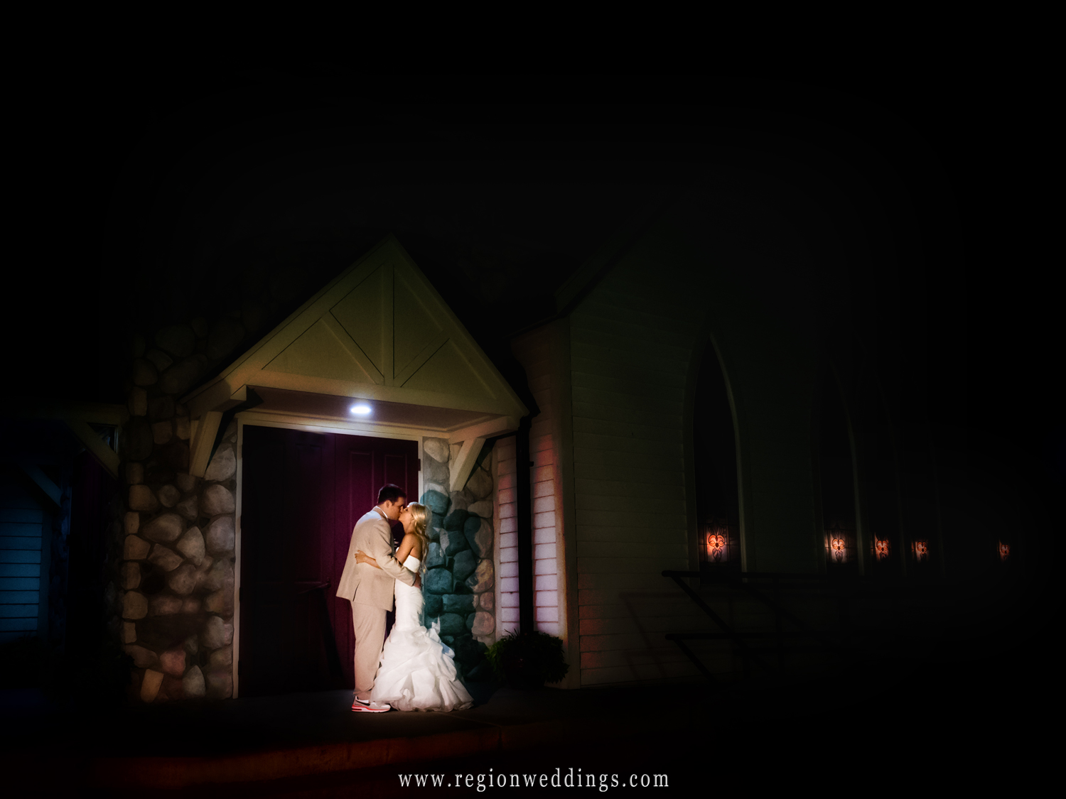 The bride and groom share a kiss underneath the evening stars in front of the Aberdeen chapel in Valparaiso, Indiana.